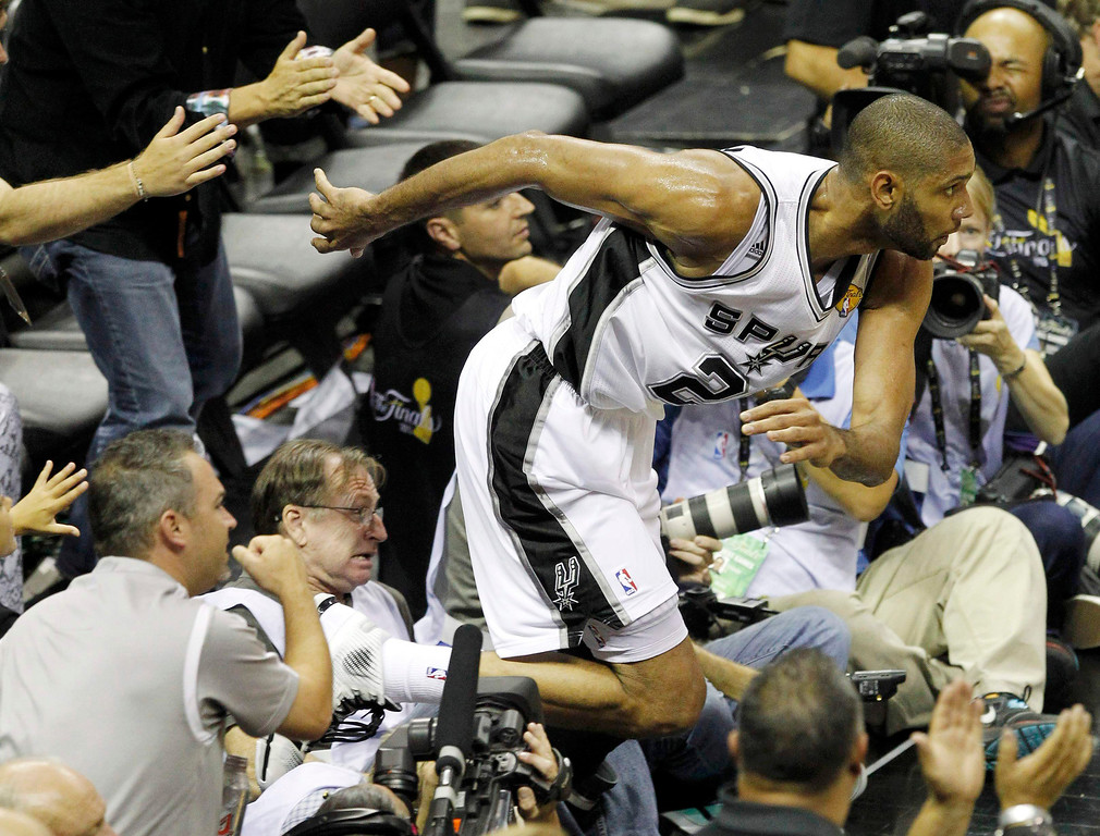 . San Antonio Spurs\' Tim Duncan runs back to the floor after running into crowd to save a ball against the Miami Heat in the third quarter during Game 3 of their NBA Finals basketball playoff in San Antonio, Texas June 11, 2013.  REUTERS/Mike Stone