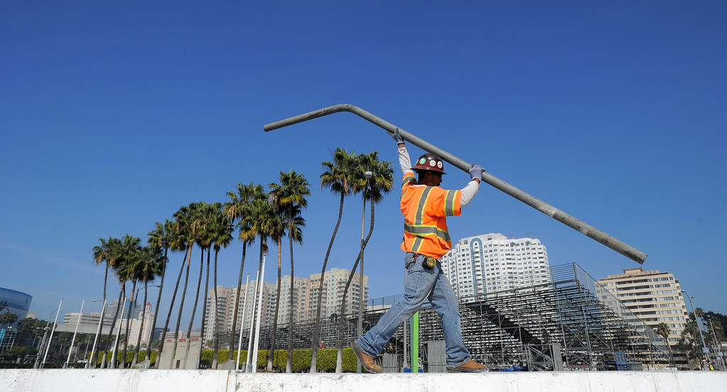 . Mayor Bob Foster and Grand Prix Association of Long Beach President & CEO Jim Michaelian kick off the first full day of LBGP track construction in Long Beach, CA on Tuesday, February 11, 2014. A track construction worker places fence posts into the temporary concrete barriers along Shoreline Drive. The 40th anniversary of the race with take place April 11-13 on the 1.97-mile course. (Photo by Scott Varley, Daily Breeze)