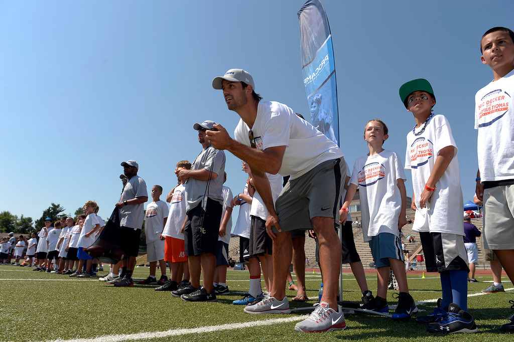 . Eric Decker times the campers in a race during camp. Demaryius Thomas and Eric Decker team up with ProCamps for their football camp held at Littleton High School July 11, 2013. Eric Decker and Demaryius Thomas Football ProCamp presented by Sunny D! for kids ages 6 to 14 held at the school. (Photo By John Leyba/The Denver Post)