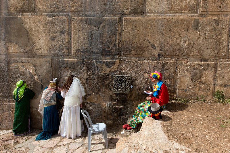 . Israeli settlers wearing various costumes pray against the large stones at the Cave of the Patriarchs at the close of the annual Purim parade in the West Bank city of Hebron, 16 March 2014. Some 800 Jewish settlers live in several communities in the city that is home to over 120,000 Palestinians. Purim celebrates the Jews\' salvation from genocide in ancient Persia, as recounted in the Scroll of Esther, as it a time of joyous celebrations, wearing costumes and public drinking.  (EPA/JIM HOLLANDER)