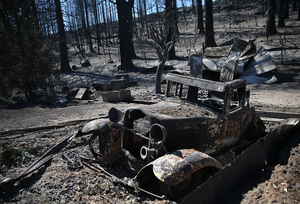 . he burned shell of a vintage car sits in the rubble of a destroyed home on September 16, 2014 in Weed, California. A fast moving wildfire fueled by high winds ripped through the town of Weed on the afternoon of September 15, burning 100 structures including the high school and lumber mill.  (Photo by Justin Sullivan/Getty Images)