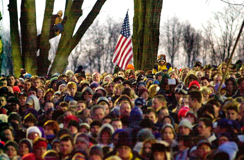 . A portion of the record Groundhog Day crowd of some 25,000 sings the National Anthem early Saturday Feb. 2, 2002 on Gobbler\'s Knob in Punxsutawney, Pa. At daybreak Punxsutawney Phil, the weather prognosticating groundhog emerged to see his shadow, thereby predicting six more weeks of winter weather. (AP Photo/Gene J. Puskar)