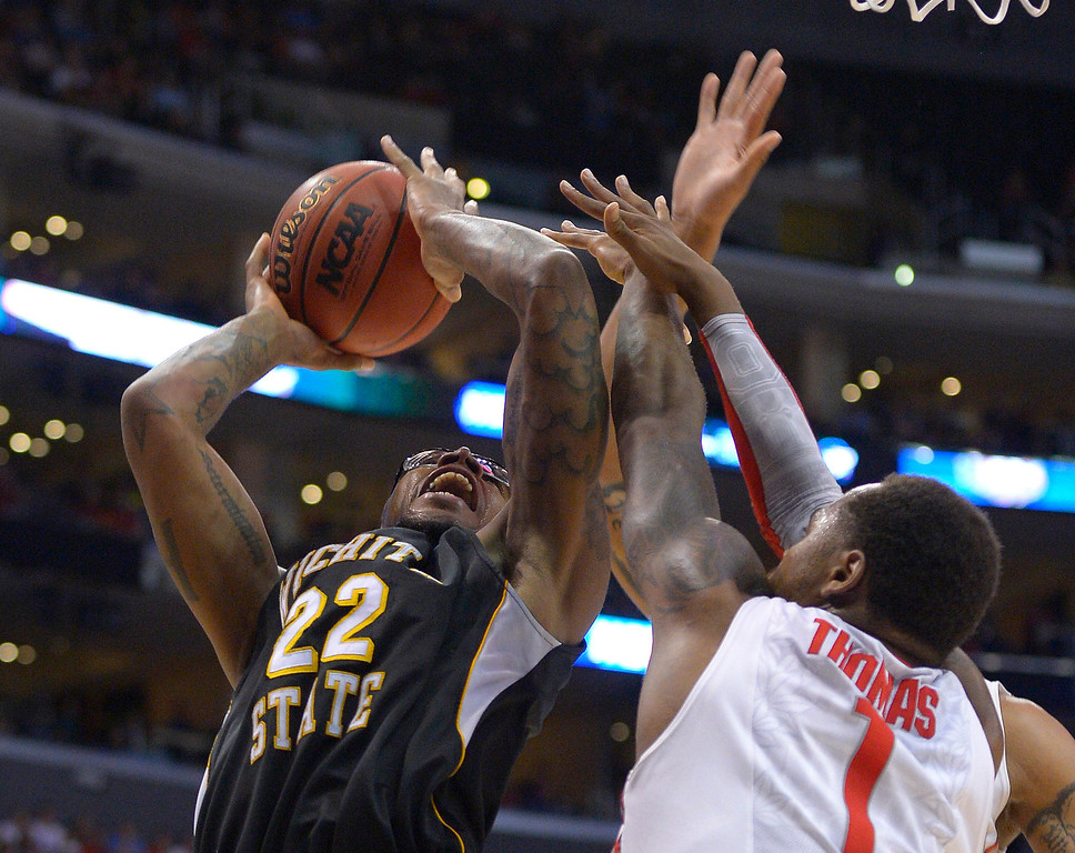 . Wichita State forward Carl Hall, left, shoots against Ohio State\'s Deshaun Thomas (1) and another defender during the first half of the West Regional final in the NCAA men\'s college basketball tournament, Saturday, March 30, 2013, in Los Angeles. (AP Photo/Mark J. Terrill)