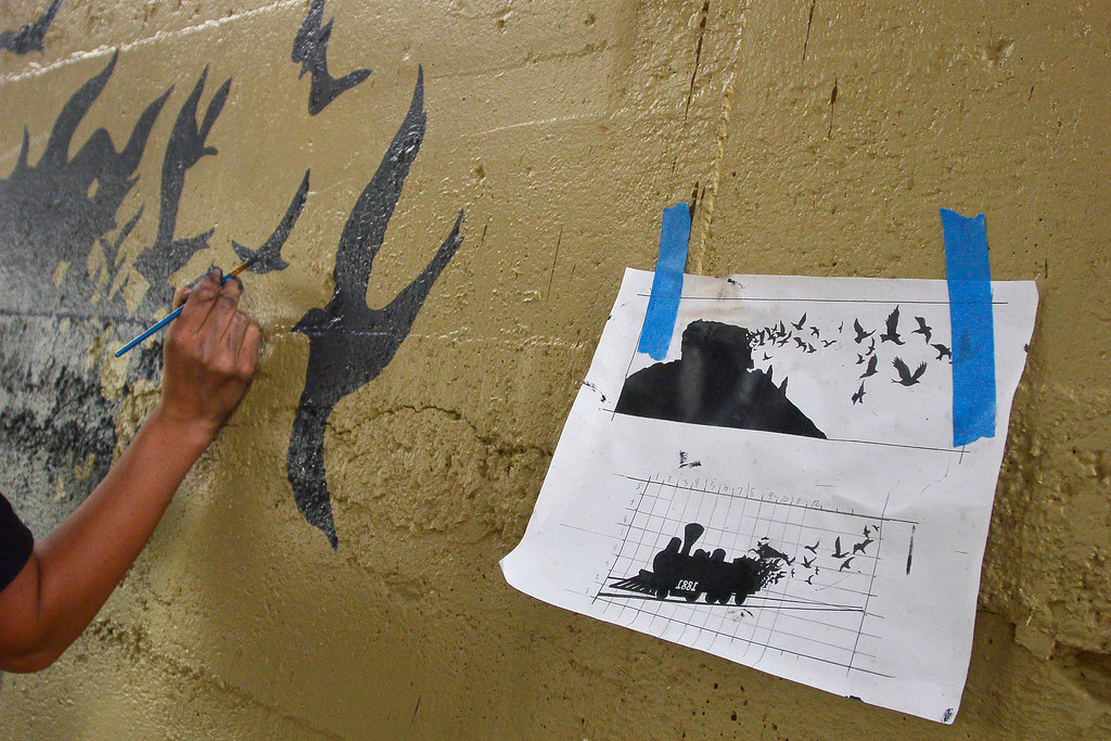 . Police officer Renee Tremaine finishes up painting birds with the train scene at Hangmans Gulch underpass. (Photo by John Leyba/The Denver Post)