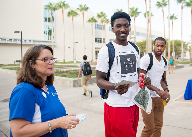 Ann Degaish(left) hands a flyer to Rashawn Thomas with the events taking place on campus the next two weeks.