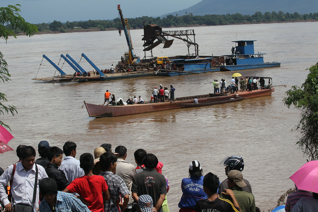 . Onlookers watch the search operation for the lost Lao Airlines plane on the banks of the Mekong River in Pakse, Laos, Thursday, Oct. 17, 2013. (AP Photo/sakchai Lalit)