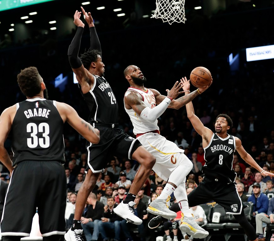 . Cleveland Cavaliers\' LeBron James (23) drives past Brooklyn Nets\' Rondae Hollis-Jefferson (24) and Spencer Dinwiddie (8) during the first half of an NBA basketball game Wednesday, Oct. 25, 2017, in New York. (AP Photo/Frank Franklin II)