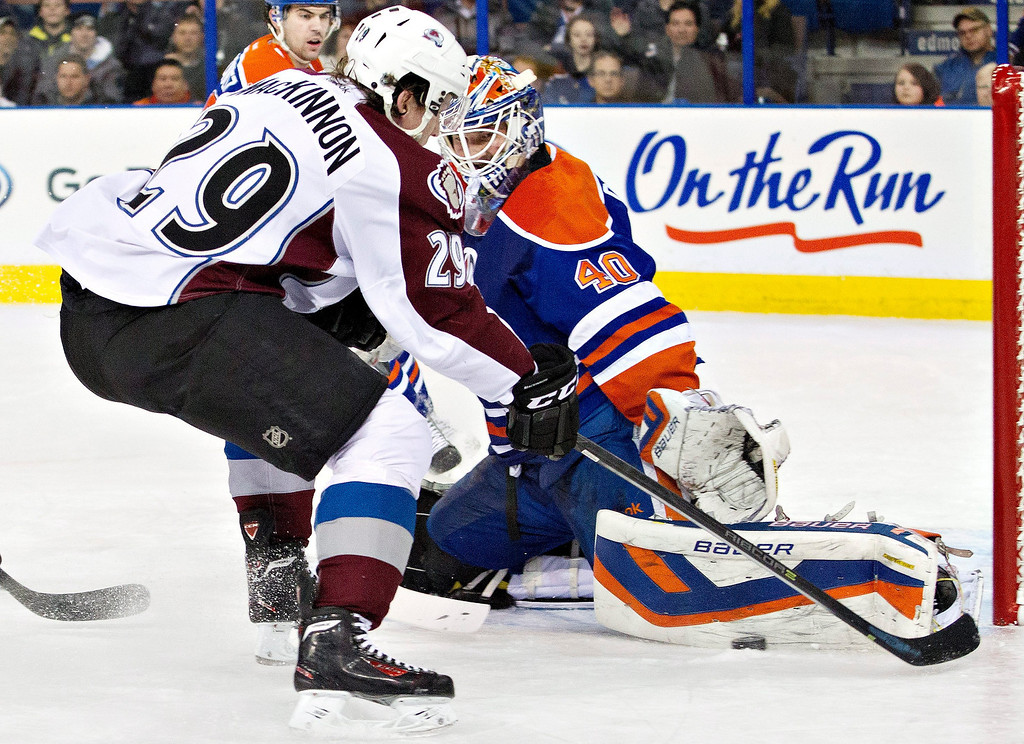 . Colorado Avalanche\'s Nathan MacKinnon (29) is sotpped by Edmonton Oilers goalie Devan Dubnyk (40) during first-period NHL hockey game action in Edmonton, Alberta, Thursday, Dec. 5, 2013. (AP Photo/The Canadian Press, Jason Franson)