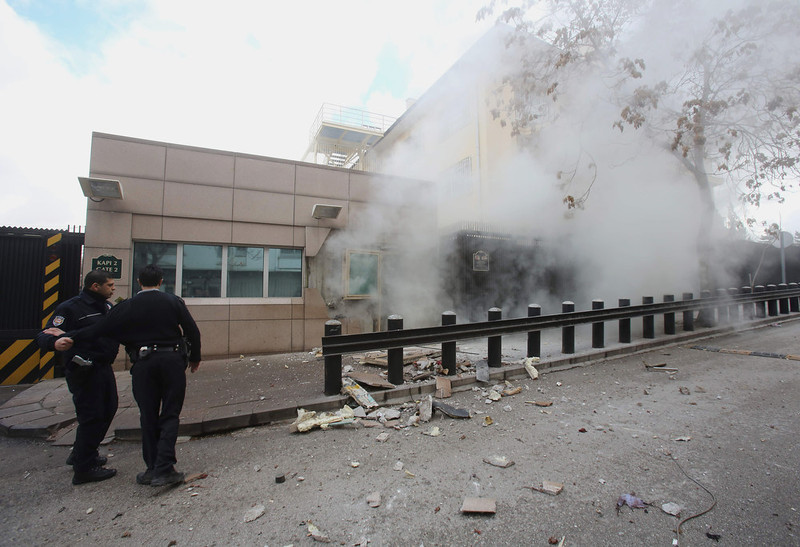 . Two police officers arrive at Gate 2 of the US embassy just minutes after a suicide bomber has detonated an explosive device at the entrance of the U.S. Embassy in the Turkish capital, Ankara, Turkey, Friday, Feb. 1, 2013, At least two people are dead, officials said. An Associated Press journalist on Friday saw a body in the street in front of an embassy side entrance. (AP Photo/Yavuz Ozden, Milliyet)