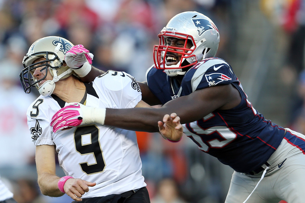 . Quarterback Drew Brees #9 of the New Orleans Saints gets off a pass while being hit by defensive end Chandler Jones #95 of the New England Patriots during the first half at Gillette Stadium on October 13, 2013 in Foxboro, Massachusetts.  (Photo by Rob Carr/Getty Images)