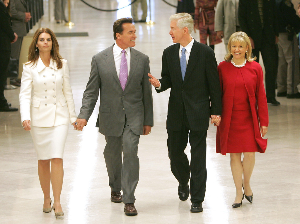. Gov. Arnold Schwarzenegger, accompanied by his wife, Maria Shriver, left, and former Gov. Gray Davis, accompanied by his wife, Sharon Davis, right, talk as they walk through the Capitol to attend the portrait unveiling ceremonies for Davis held Wednesday, Dec. 7, 2005. The portrait of the 37th governor, done by San Jose artist Robert K. Seamans, will hang in the third floor of the Capitol\'s west wing.(AP Photo/Rich Pedroncelli)