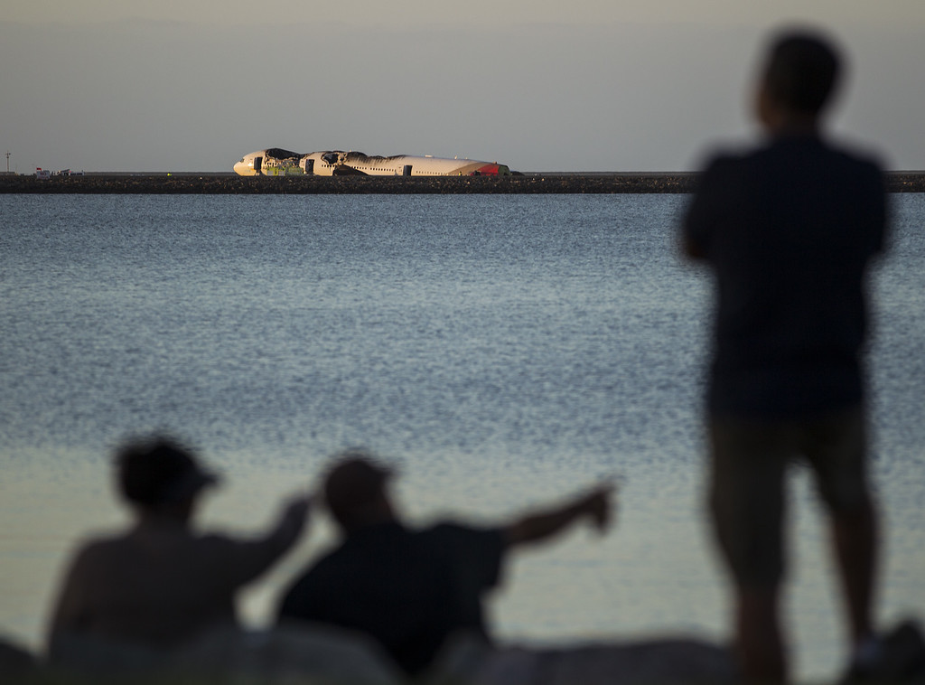 . People look out over the water toward a Boeing 777 airplane that crashed while landing at San Francisco International Airport July 6, 2013 in San Francisco, California. An Asiana Airlines passenger aircraft coming from Seoul, South Korea crashed while landing, killing two people and injuring scores of others. (Photo by Kimberly White/Getty Images)