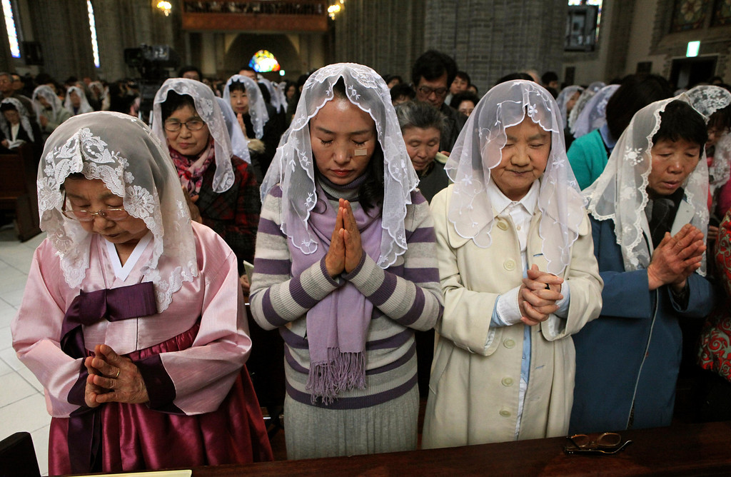 """. South Korean Catholics pray for peace on the Korean Peninsula during an annual Easter service at Myeongdong Catholic Cathedral in Seoul, South Korea, Sunday, March 31, 2013. North Korea warned South Korea on Saturday that the Korean Peninsula had entered \""""a state of war\"""" and threatened to shut down a border factory complex that\'s the last major symbol of inter-Korean cooperation.(AP Photo/Ahn Young-joon)"""