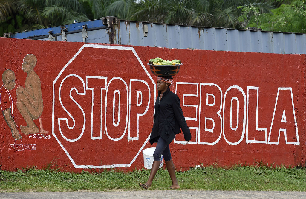 ". A woman walks past a wall bearing the message ""Stop Ebola\"" in Monrovia on September 25, 2014. World leaders were asked to pledge urgently needed aid to battle Ebola in West Africa as Sierra Leone quarantined one million people in a desperate bid to beat back the deadly virus. US President Barack Obama warned that not enough was being done to tackle the crisis that has left close to 3,000 dead and is spreading at an alarming pace. PASCAL GUYOT/AFP/Getty Images"