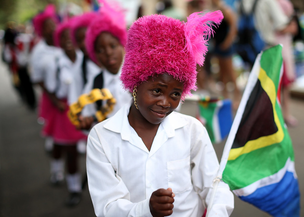 . A group of girls perform a drum and dance routine outside the home of former South African President Nelson Mandela on the day that the iconic leader was laid to rest in his home village on December 15, 2013 in Johannesburg, South Africa.  Mr. Mandela passed away on the evening of December 5, 2013 at his home in Houghton at the age of 95. Mandela became South Africa\'s first black president in 1994 after spending 27 years in jail for his activism against apartheid in a racially-divided South Africa.  (Photo by Justin Sullivan/Getty Images)