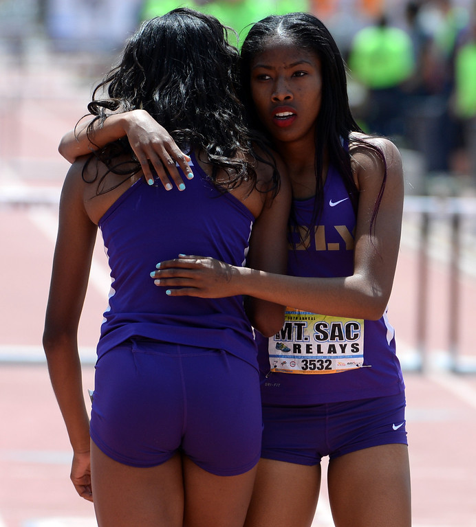 . Long Beach Poly\'s Ebony Crear, left, is hugged by Kymber Payne after the 300 meter hurdles Invitational during the Mt. SAC Relays in Hilmer Lodge Stadium on the campus of Mt. San Antonio College in Walnut, Calif., on Saturday, April 19, 2014.  (Keith Birmingham Pasadena Star-News)