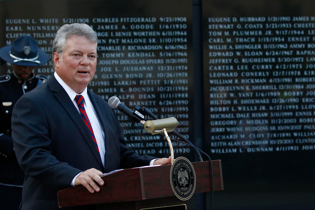 . Mississippi Attorney General Jim Hood stands before the Statewide Fallen Officers Memorial as he addresses attendees at the Mississippi Law Enforcement Memorial Candlelight Vigil in Jackson, Miss., Tuesday, May 15, 2018. (AP Photo/Rogelio V. Solis)