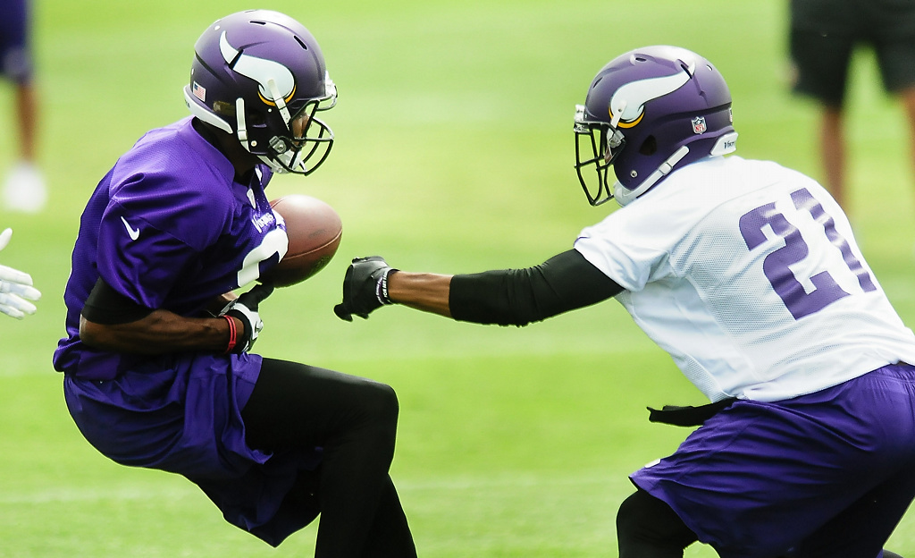 . Minnesota Vikings wide receiver Jerome Simpson, left, has the ball stripped for a fumble by cornerback Josh Robinson at Vikings training camp in Mankato, Minn., on Friday, July 26, 2013. (Pioneer Press: Ben Garvin)
