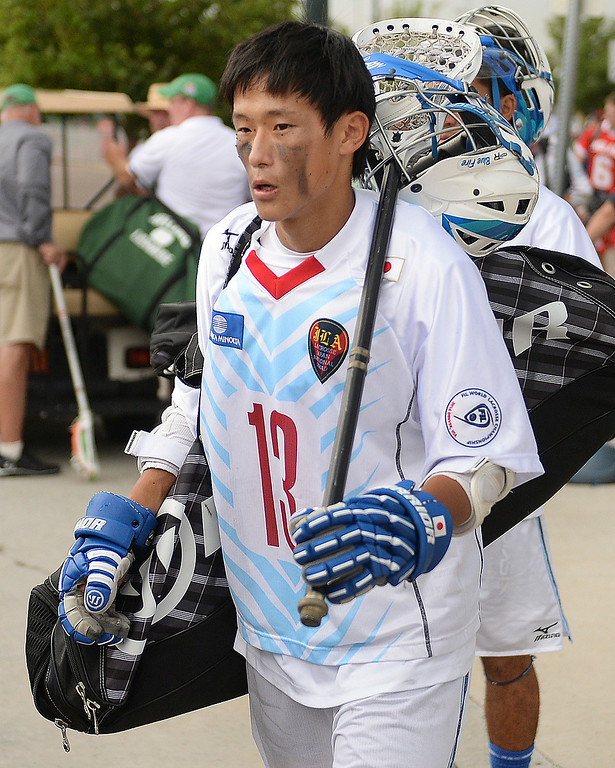 . Japan midfielder Gaku Iwano headed for shelter after a lightning delay was called Tuesday night, July 15, 2014.  Japan was in the middle of a match against England when severe weather rolled over Commerce City.