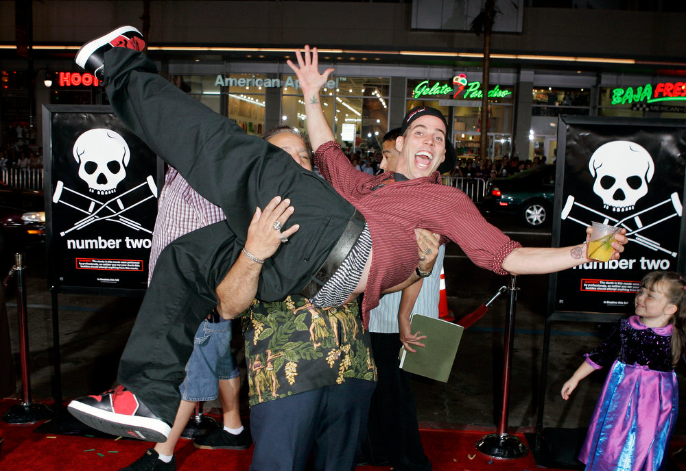 Description of . Steve-O is picked up by adult film star Ron Jeremy at the premiere of