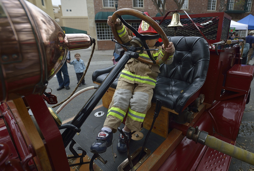 . TORRANCE, CALIF. USA -- Kie Bresler struggles to reach the pedals of an old fire truck in Torrance, Calif., on April 14, 2013. The Old Torrance Festival Day is a charity fundraiser that will benefits the South Bay Police and Fire Memorial Foundation and the Torrance Relay for Life. Photo by Jeff Gritchen / Los Angeles Newspaper Group