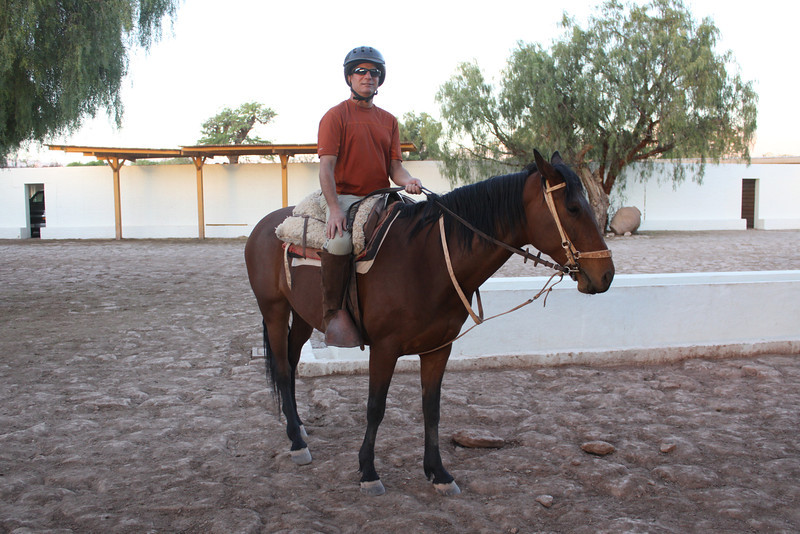 Cliff on horse named Sobroso, after ride over dunes.