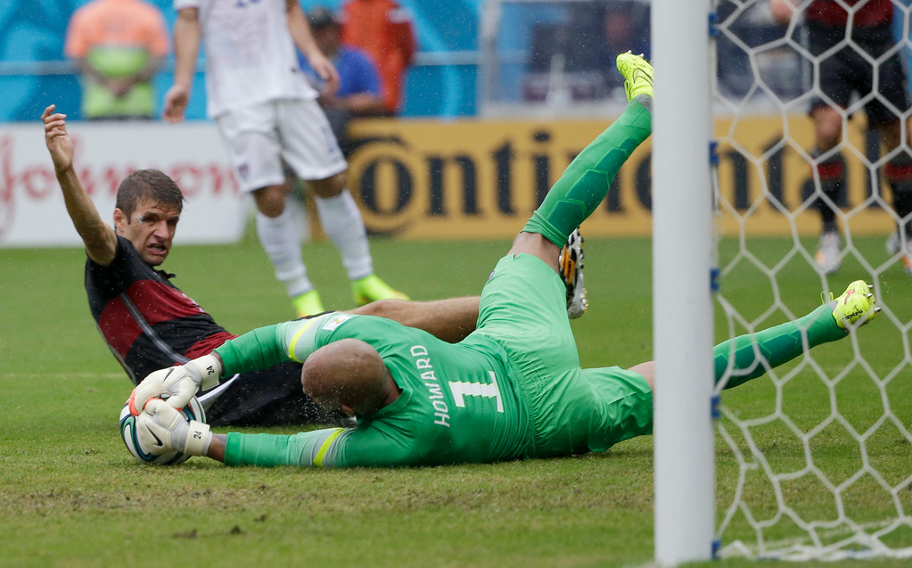 . United States\' goalkeeper Tim Howard dives to make a save on Germany\'s Thomas Mueller during the group G World Cup soccer match between the USA and Germany at the Arena Pernambuco in Recife, Brazil, Thursday, June 26, 2014. (AP Photo/Ricardo Mazalan)