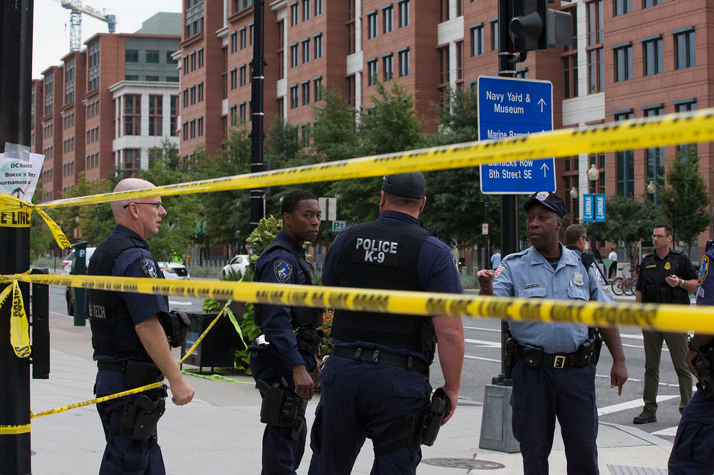 . Police work the scene on M Street, SE in Washington near the Washington Navy Yard on Monday, Sept. 16, 2013. The U.S. Navy says one person is injured after a shooting at a Navy building in Washington. Police and emergency crews gathered Monday morning outside the Naval Sea Systems Command Headquarters building, where the shooting was reported.  (AP Photo/Jacquelyn Martin)