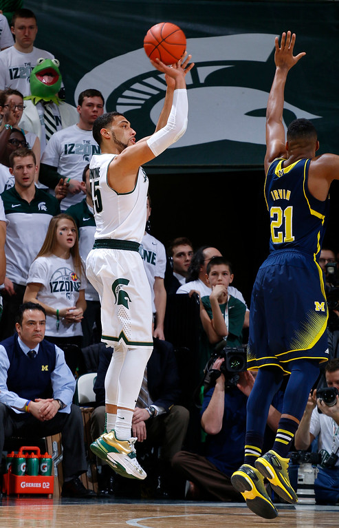 . Michigan State\'s Denzel Valentine, left, shoots a 3-pointer against Michigan\'s Zak Irvin (21) during the first half of an NCAA college basketball game, Sunday, Feb. 1, 2015, in East Lansing, Mich. (AP Photo/Al Goldis)