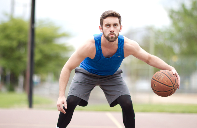 male model with beard playing basketball
