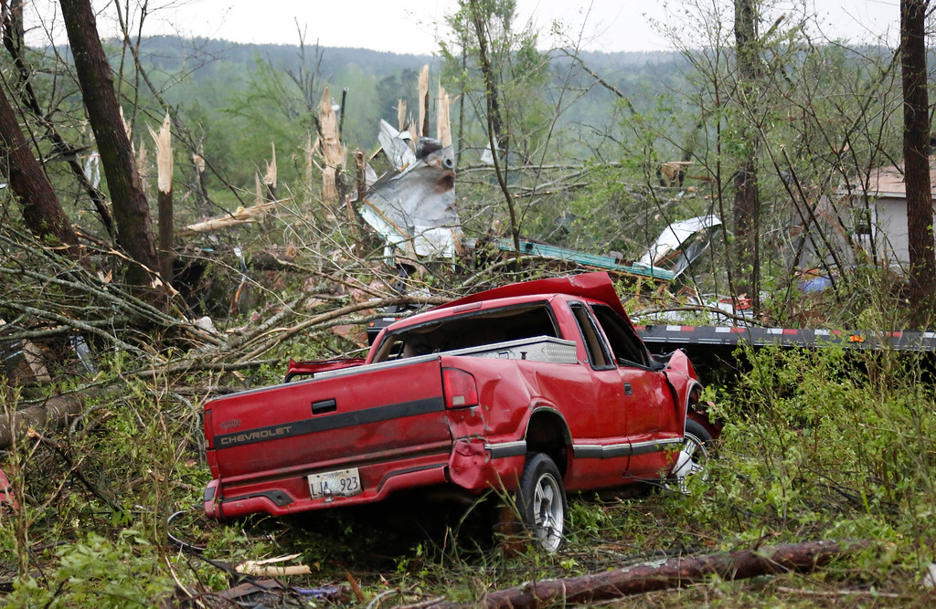 . Torn tree tops and damaged trucks are evidence of the tornado that hit Four Corners, Miss., Monday, April 28, 2014. Tornados flattened homes and businesses, flipped trucks over on highways and injured numerous  people in Mississippi and Alabama on Monday as a massive, dangerous storm system passed over several states in the South, threatening additional twisters as well as severe thunderstorms, damaging hail and flash floods. (AP Photo/Rogelio V. Solis)