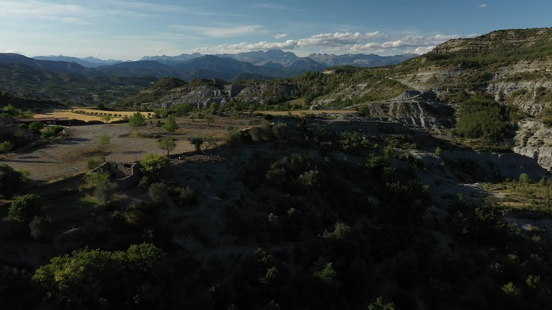 Available in 4k - Aerial drone video showing the typical badlands landscape of Sierra de Guara near the village of Arcusa with the Spanish Pyrenees mountain range in the background near the time of sunset, sunrise.