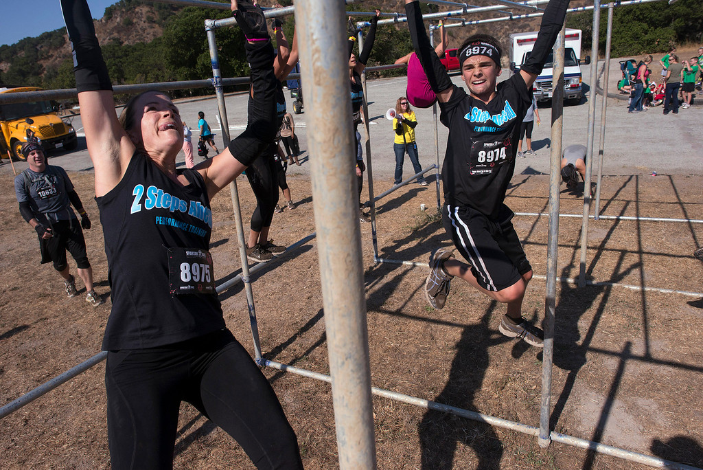 . Tiffany and Reno Ditullo traverse a set of monkey bars Saturday, August 10th, 2013 during the first annual Monterey Spartan Race, which was held this year at Toro Park. (Matthew Hintz/Monterey County Herald)