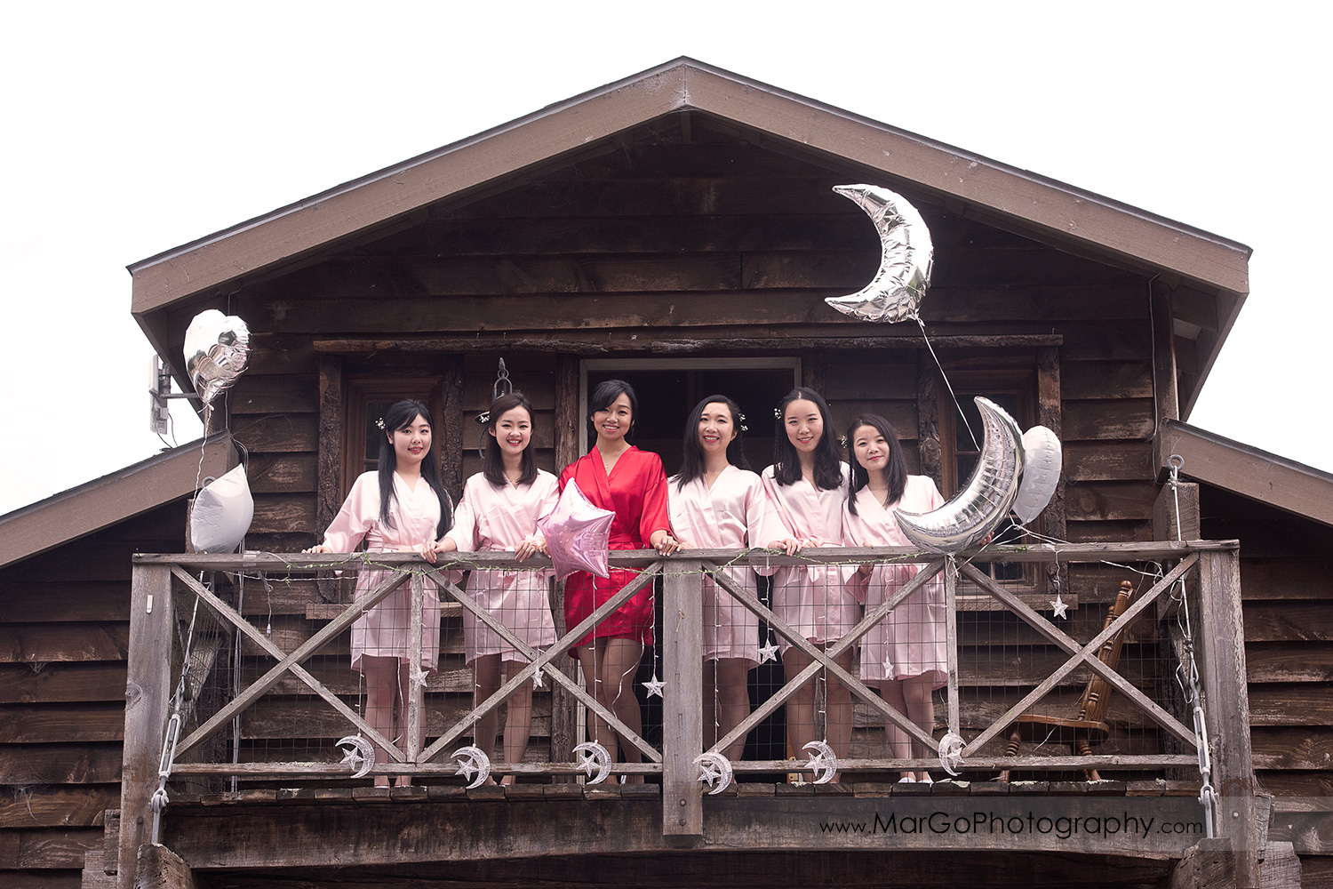 bride in red robe and bridesmaids in pink robes on the balcony at Long Branch Saloon & Farms in Half Moon Bay