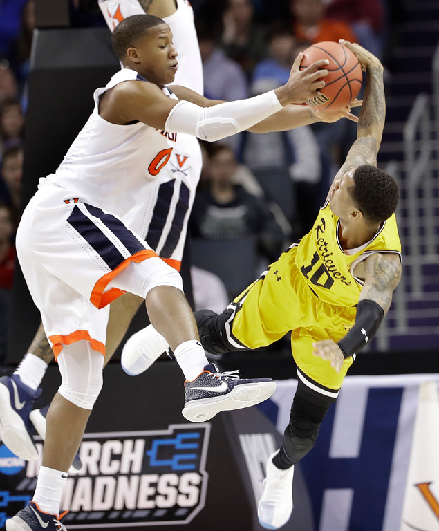 . Virginia\'s Devon Hall (0) ties up UMBC\'s Jairus Lyles (10) during the first half of a first-round game in the NCAA men\'s college basketball tournament in Charlotte, N.C., Friday, March 16, 2018. (AP Photo/Gerry Broome)