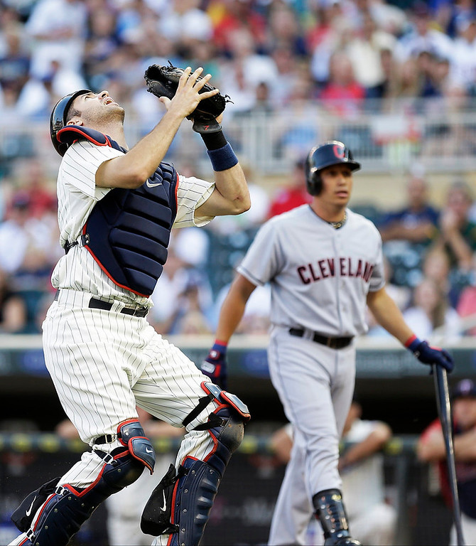 . Cleveland Indians\' Asdrubal Cabrera, right, heads back to the dugout as Minnesota Twins catcher Joe Mauer fields his pop foul in the first inning. (AP Photo/Jim Mone)