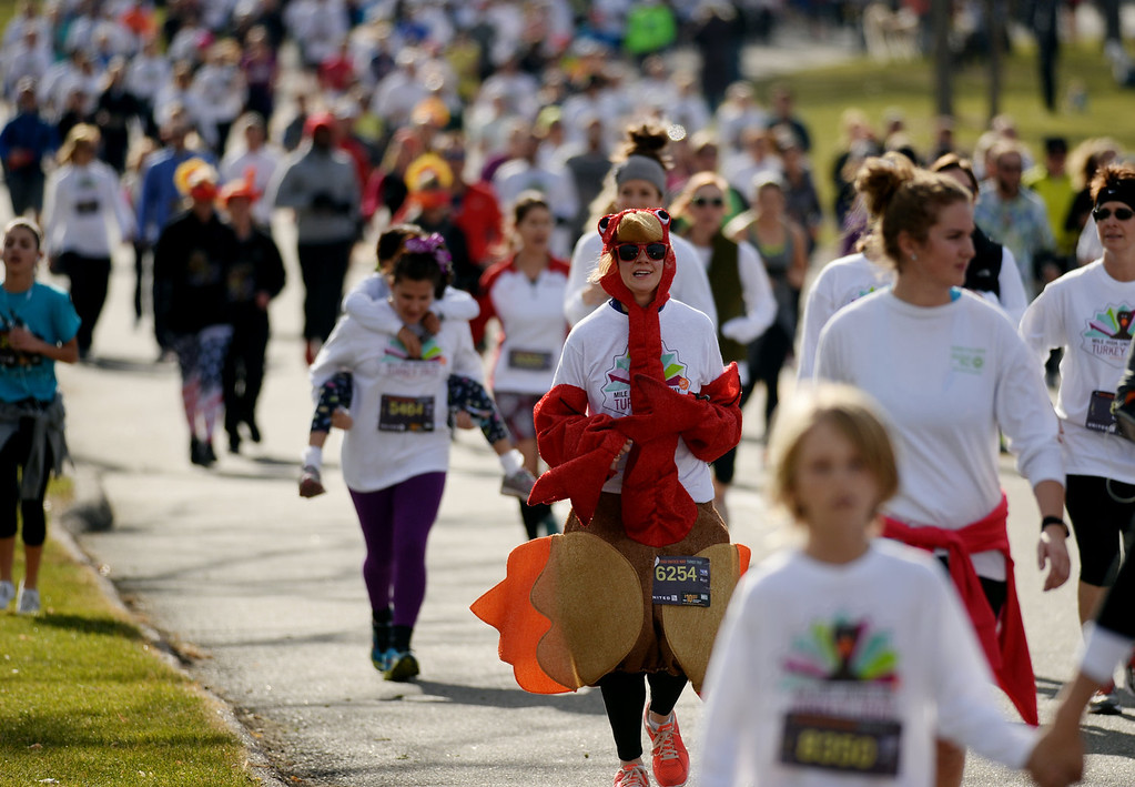 . Ariel Steeber, 24, sports a turkey costume from New York among runners in the 40th Annual Turkey Trot in Washington Park in Denver, Colorado on November 28, 2013. Denver\'s largest Thanksgiving Day run benefits United Way and goes for 4 miles. (Photo by Hyoung Chang/The Denver Post)