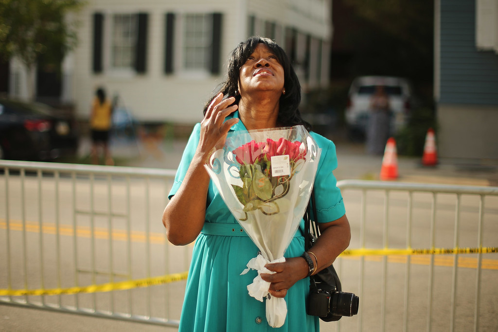 . Lucinda Magwood pauses to pray in front of the historic Emanuel African Methodist Church where nine people were shot to death earlier this week June 20, 2015 in Charleston, South Carolina. The Charleston community continues to grieve the murder of nine churchgoers as suspect Dylann Storm Roof, 21, was captured and charged in their deaths on Thursday.  (Photo by Chip Somodevilla/Getty Images)
