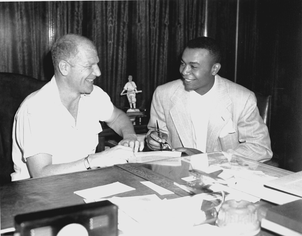 . President of the Cleveland Indians, Bill Veeck, left, gives his newest player, Larry Doby, a big smile at Comisky park in Chicago, July 5, 1947 after Doby had finished signing a contract with the Indians. Doby is the first black person in the American Baseball League. (AP Photo)