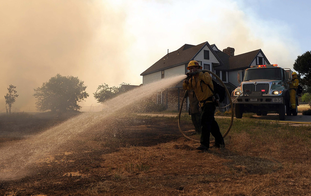 . A U.S Forest Service firefighter battle flames near a home on a 1,500 acre brush fire Wednesday May 1, 2013 in Banning. LaFonzo Carter/Staff Photographer