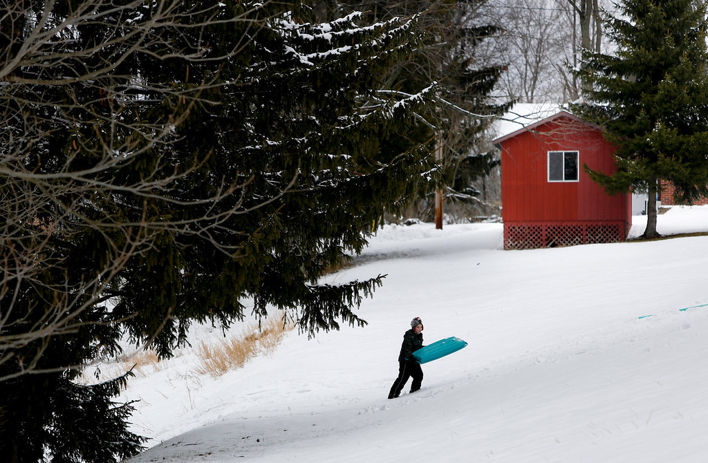 . Garrett Strahin, 8, climbs a hill while carrying his sled in Masontown, W.Va., on Wednesday, March 6, 2013. A late winter storm dumped nearly a foot of snow Wednesday in West Virginia, closing schools in more than half the state and leaving more than 20,000 customers without power. (AP Photo/David Smith)