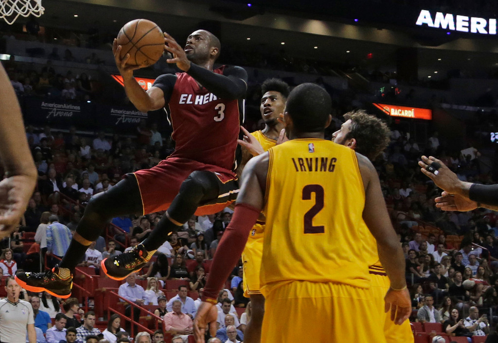 . Miami Heat guard Dwyane Wade (3) shoots over Cleveland Cavaliers guard Kyrie Irving (2) during the second half of an NBA basketball game, Saturday, March 19, 2016, in Miami. (AP Photo/Lynne Sladky)
