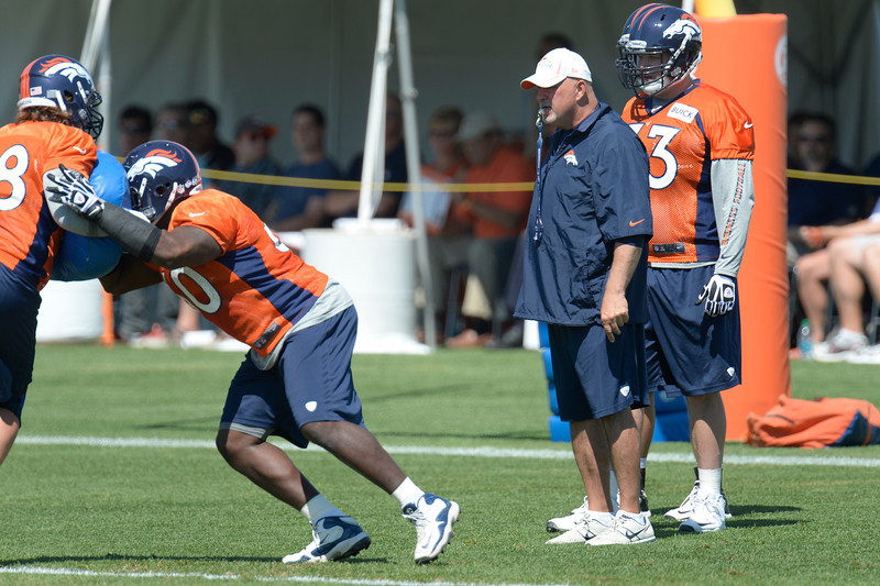. Denver Broncos offensive line coach Dave Magazu watches the line run through drills during practice August 19, 2013 at Dove Valley (Photo by John Leyba/The Denver Post)