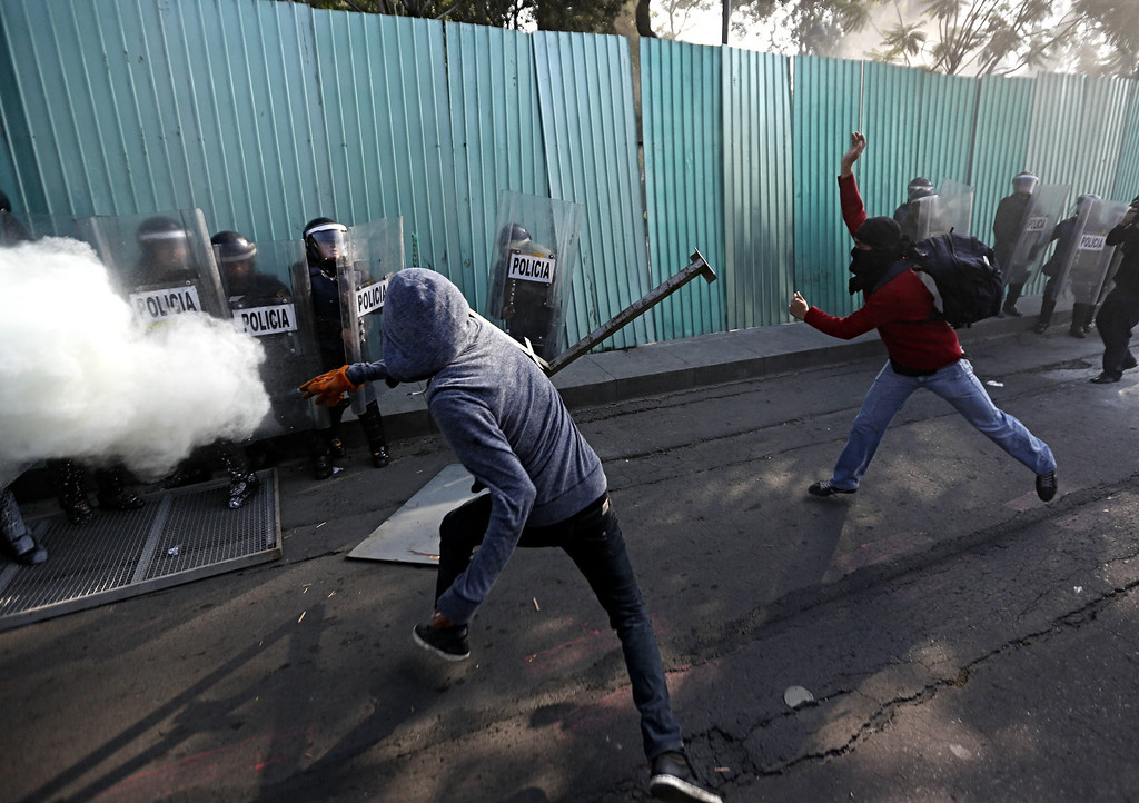 . Masked protesters clash with riot police during a march marking the anniversary of the Tlatelolco massacre in Mexico City, Wednesday, Oct. 2, 2013. Mexico commemorated the 45th anniversary of the massacre of students holding an anti-government protest, killed by men with guns and soldiers ten days before the 1968 Summer Olympics celebrations in Mexico City. (AP Photo/Eduardo Verdugo)