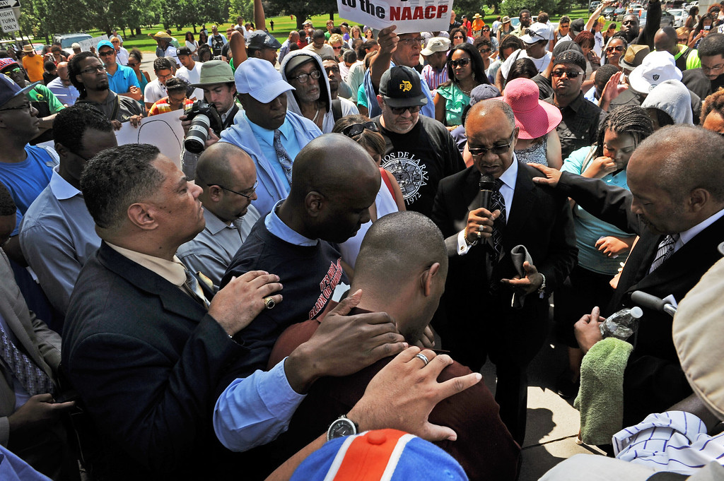 """. Reverands and members of the African American community of Denver pray together  during the rally in City Park in Denver, CO on July 14, 2013.  Several hundred people turned out  to show their disappointment in the acquittal of George Zimmerman in the murder trail of Trayvon Martin.  Zimmerman is the Florida man who shot and killed Trayvon Martin. \""""We will not erase the conversation of race,\"""" said Jeff Fard, founder of Brother Jeff\'s Cultural Center in the Five Points neighborhood. \""""Don\'t be afraid to say if Trayvon Martin was a white man he would be alive today.\""""  Photo by Helen H. Richardson/The Denver Post)"""