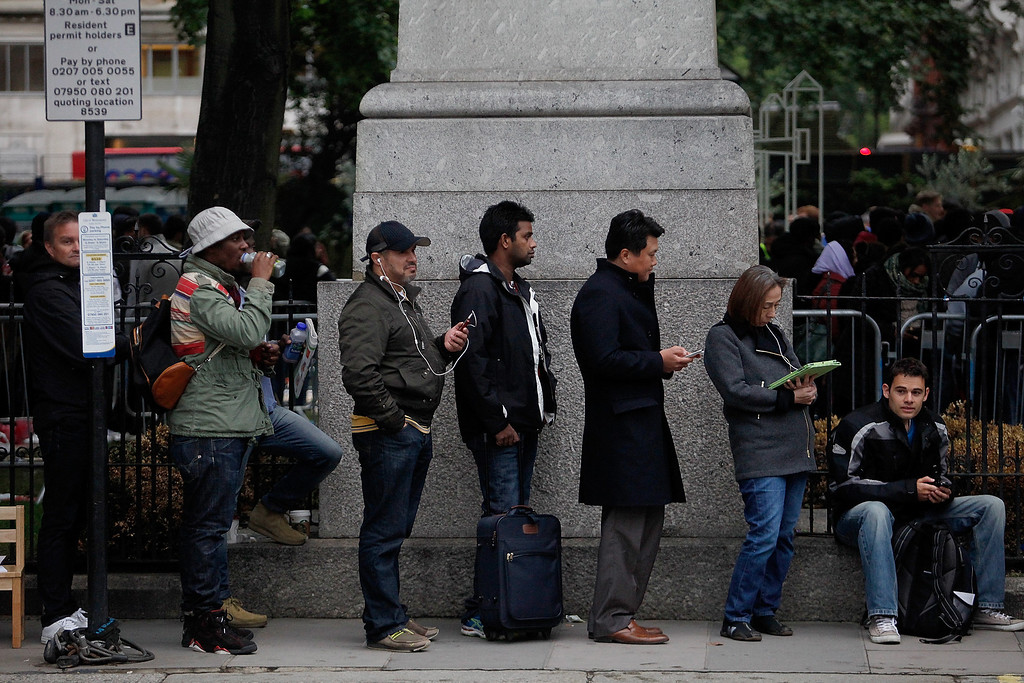 . People queue around the block of the Apple store for the new iPhone5S, on Regent Street on September 20, 2013 in London, England. Some consumers have queued for five days, sleeping in makeshift tents, to be the first to own the new updated iPhone. (Photo by Mary Turner/Getty Images)