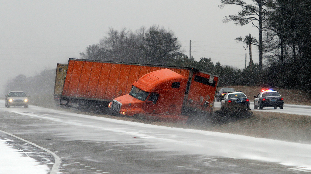 . A truck slides into the median while trying to avoid another wrecked truck in the snow  on I-65 several road   Tuesday, Jan. 28, 2014, in Clanton, Ala.  A rare storm left a slippery layer of ice and snow across a region unaccustomed to dealing with the wintry threat.   (AP Photo/Butch Dill)