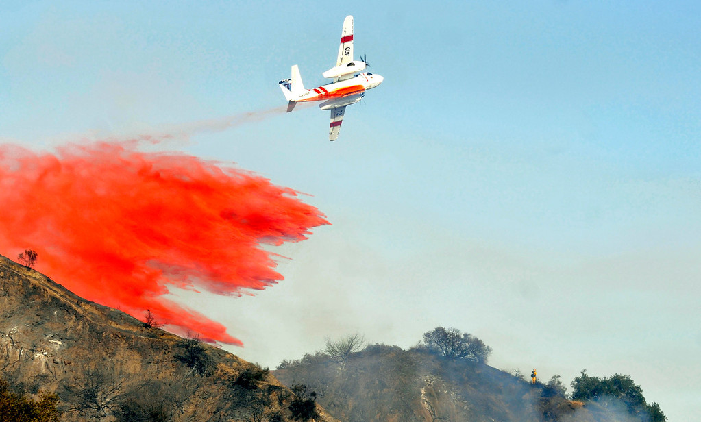 . A lone firefighter is visible on the ridge ahead of the tanker plane.  Firefighters from all surrounding agencies came in to help the Monrovia Fire Dept. battle a major wildfire in the foothills above their city, Saturday April 20, 2013.  (Mike Mullen)