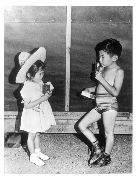 """""""Two youngsters at the Japanese Assembly Center enjoy America's typical dessert -- ice cream.""""--caption on photograph"""