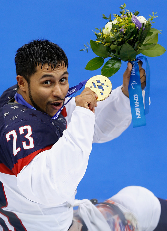 . Rico Roman of USA holds up his gold medal after his team won the Ice Sledge Hockey Gold Medal match between Russia and USA at the Shayba Arena during day eight of the 2014 Paralympic Winter Games on March 15, 2014 in Sochi, Russia.  (Photo by Harry Engels/Getty Images)